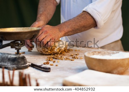 Male hands knead the dough with walnuts