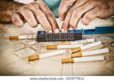 Male hands making cigars with rollings filled with tobacco to satisfy his habit and to smoke handmade cigarettes - stock photo