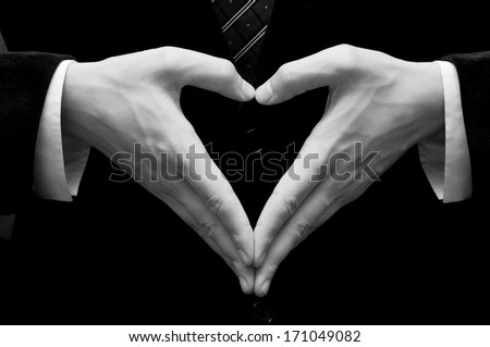 male hands making heart shape isolated on black - stock photo