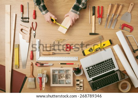 Male hands measuring a wooden plank with a tape measure with DIY work tools all around on a work table, top view - stock photo