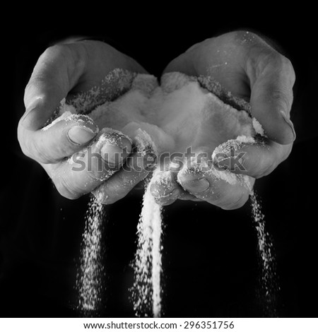Male hands on black with salt pouring through signifying sadness and loss of control - stock photo