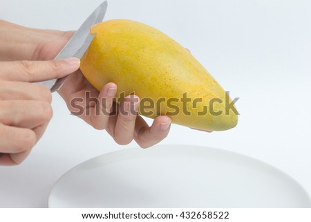 male hands peeling mango - stock photo