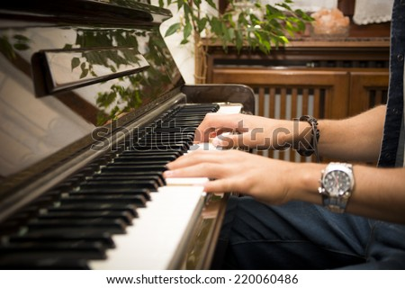 Male hands playing piano indoors inside house - stock photo