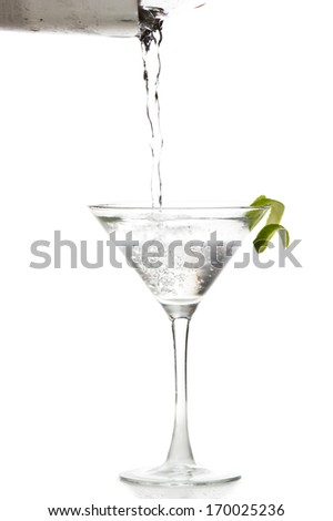 male hands pouring a vodka martini in to a chilled glass with a lime garnish