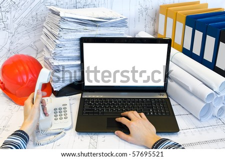 Male hands printing on loaptop and holding handset of phone. Documents are around. - stock photo