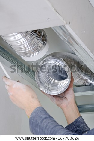 Male hands setting up ventilation system indoors - stock photo
