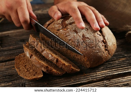 Male hands slicing bread on brown wooden background - stock photo
