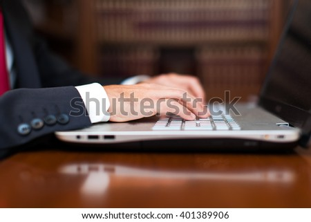 Male hands typing on a laptop keyboard - stock photo