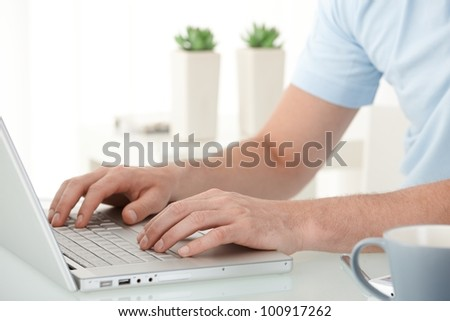 Male hands typing on laptop computer keyboard, closeup portrait. - stock photo