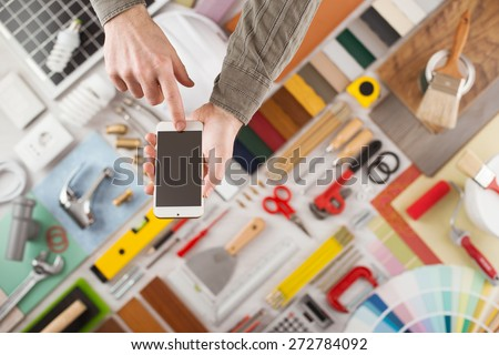 Male hands using a touch screen smart phone, build and home renovation tools on background, top view - stock photo