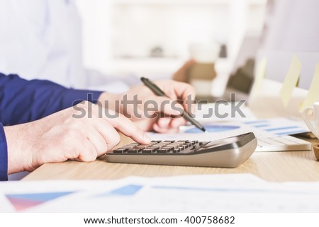 Male hands using calculator on business charts - stock photo