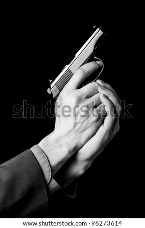 Male hands with gun on black background - stock photo