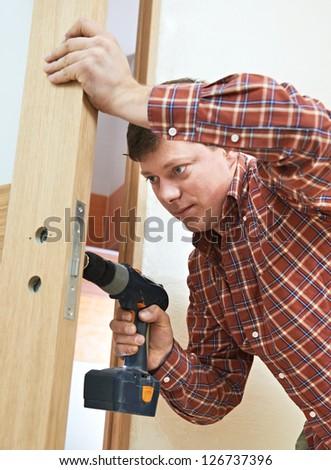Male handyman carpenter at interior wood door lock installation - stock photo