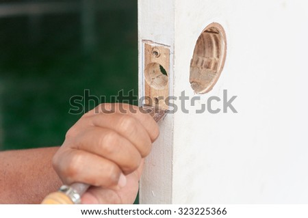 Male handyman carpenter at interior wood door lock installation.Selective focus. Very shallow Depth of Field, for soft background. - stock photo