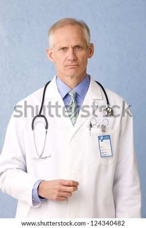 Male healthcare professional looking to the camera concerned with stethoscope and medical identification card three quarter view on blue background