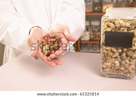 Male herbalist with Chinese medicinal herbs - stock photo