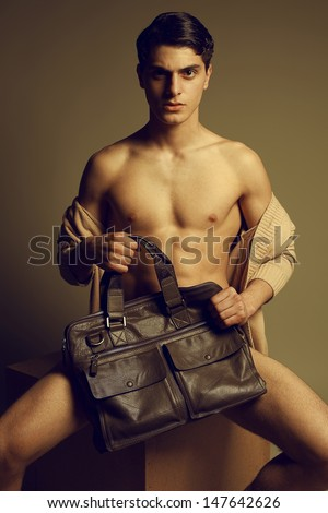 Male high fashion concept. Portrait of a handsome male model sitting on a wooden cube in trendy cardigan, holding leather bag. Perfect skin & haircut. Vogue style. Studio shot
