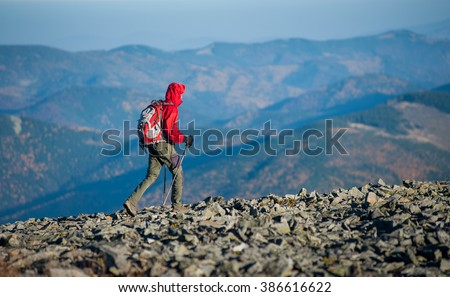 Male hiker backpacker walking on the rocky mountain ridge with beautiful mountains on background. Man is wearing red jacket and has trekking sticks and backpack on. Sunny fall day. - stock photo