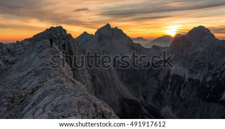 Male hiker enjoying majestic sunset in the mountains