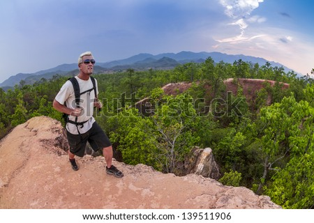 Male hiker in white shirt and backpack walking along narrow mountain path in red canyon Resubmit - Reprocessed - stock photo