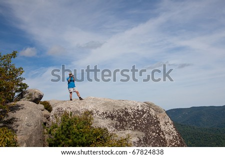 Male hiker looks over valley in the Shenandoah on a climb of Old Rag and takes a photo - stock photo