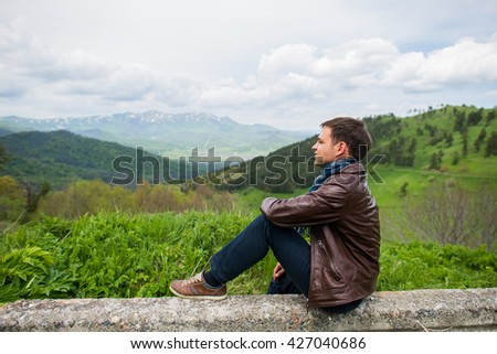 Male hiker relaxing on top of a mountain - stock photo