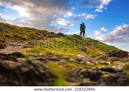 Male hiker standing in high peak - stock photo