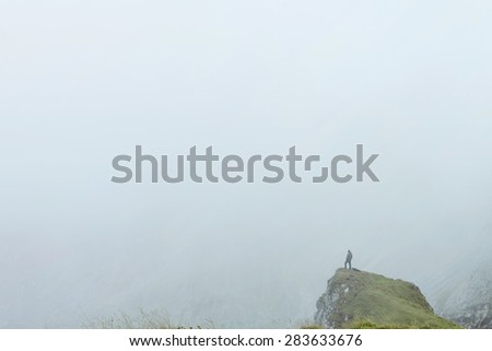 Male hiker standing in mist on edge of high steep cliff - stock photo