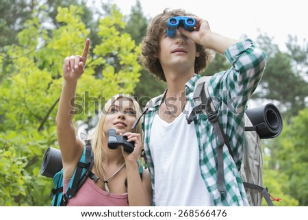 Male hiker using binoculars while girlfriend showing something in forest - stock photo