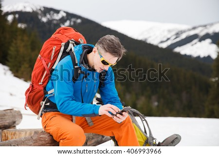 Male hiker using smartphone in winter mountains. Concept of success living and free traveling, active leisure, health care and well being. - stock photo