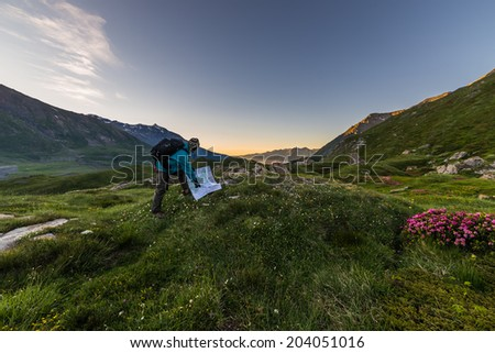 Male hiker with backpack watching trekking map at sunrise in the italian french Alps. - stock photo