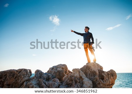 Male hiker with photo camera stands on the rock over the blue sky and looking on horizon