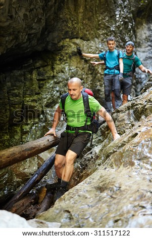 Male hikers going down through a very difficult canyon - stock photo