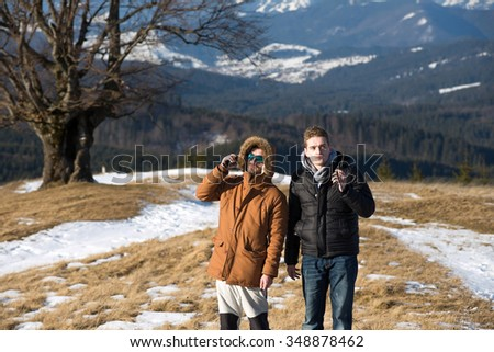 Male hikers using walkie talkie against mountain peaks. - stock photo