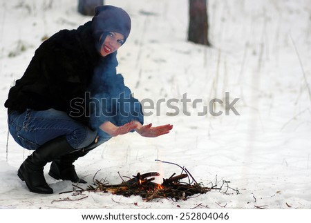 Male hikers warming hands at campfire in forest - stock photo