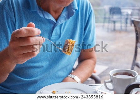 Male holds fork with tasty piece of cake   - stock photo