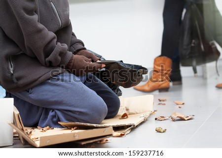 Male homeless begging on a subway station  - stock photo