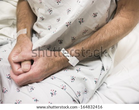 Male hospital patient wearing gown and ID bracelet - stock photo