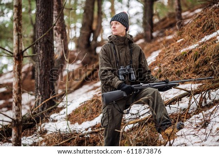 male hunter ready to hunt, holding gun and walking in forest. hunting and people concept