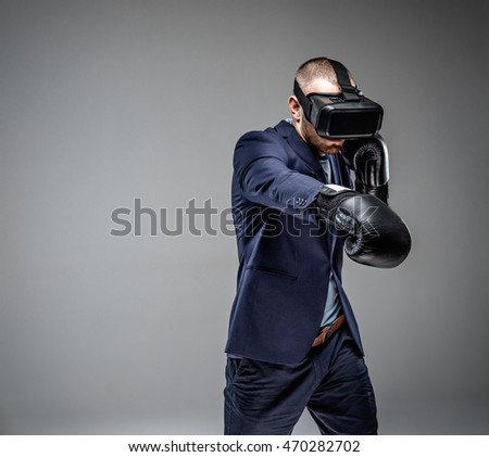 Male in a suit fighting with virtual reality glasses on his head.