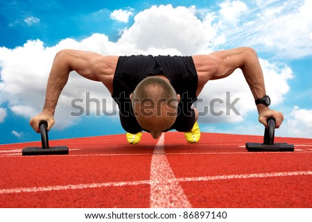 Male in middle ages makes push ups on a racetrack