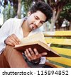 Male Indian / Asian college student reading book over the bench. - stock photo