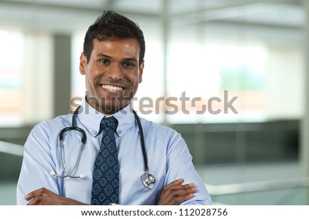 Male Indian General Practitioner or GP standing in hospital with background out of focus. - stock photo