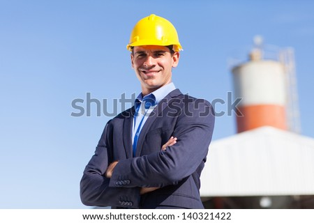 male industrial engineer in mining site with arms crossed - stock photo