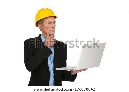 male inspector in helmet working on computer. specialist looking at plan and calculating wall - stock photo