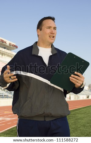 Male instructor holding clipboard - stock photo