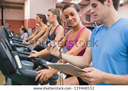 Male instructor showing stopwatch in the gym - stock photo