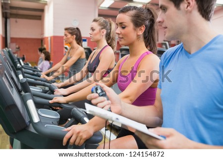 Male instructor with stopwatch in the gym - stock photo