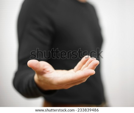 male is standing  and shows outstretched hand with open palm - stock photo