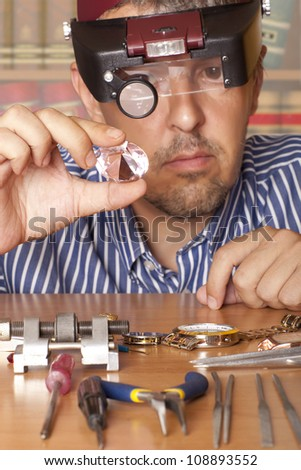Male jeweler looking through a magnifier to check for flaws in a diamond.  Focus on diamond